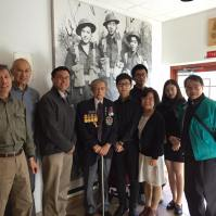 Veteran Bing Wong stands in front of a photograph of himself as a young soldier with CCMS President King Wan and PCHC Directors, Members, and Volunteers
