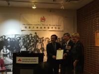 King Wan presented with certificate on behalf of the Hon. Teresa Wat