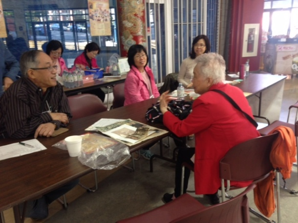 Mrs Wong showing her family photos to Godfrey & volunteers